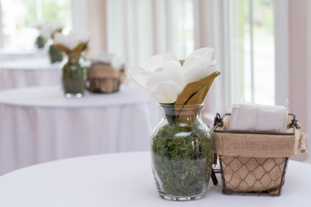 magnolia flower centerpiece and a basket of napkins on a white table