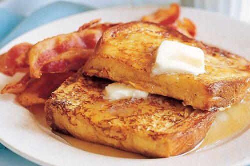 a plate of french toast with butter, syrup, and strips of bacon